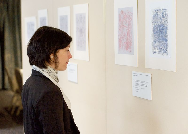 a woman observes mono print exhibition